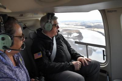 Governor Parson looks out of a Black Hawk with Emergency Management Personal to survey the flooded areas of Northwest Missouri.